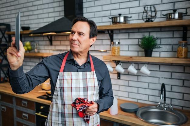 Ernsthafter mann in der schürze stehen in der küche und betrachten teller in der hand. er trocknet es. auch kerl halten küchentuch.