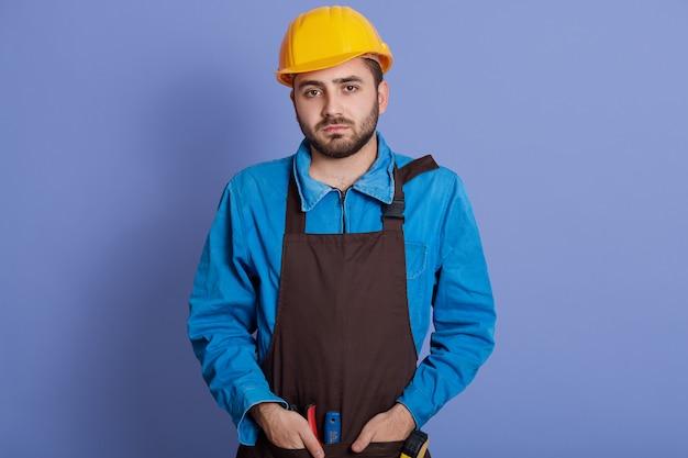 Ernsthafter mann macht renovierung zu hause, trägt schutzhelm und braune schürze, beschäftigt mit der reparatur, hat gesichtsausdruck gestört.