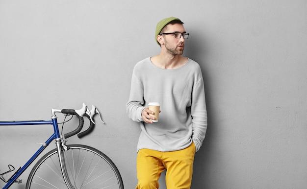 Ernsthafter mann mit borsten, der beiseite schaut, während er die hand in der tasche hält und pappbecher mit kaffee hält, seinen freund bemerkt, während er nach langer reise allein in den bergen pause macht. lebensstil und hobby