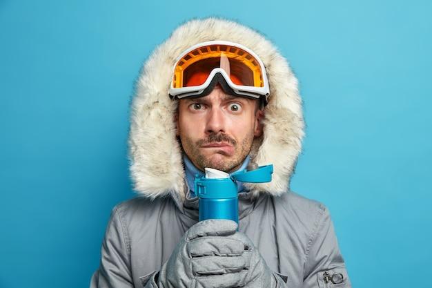 Ernsthafter mann zittert vor kälte, nachdem er an einem frostigen wintertag ski gefahren ist. er hält eine flasche mit heißem getränk, trägt eine skibrille und eine warme jacke.
