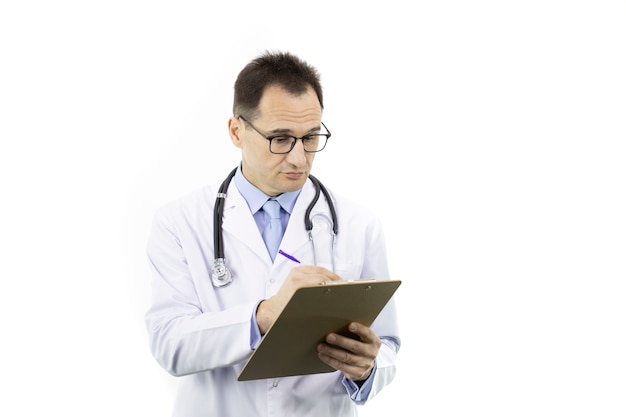 Ernsthafter medizinischer arbeiter im weißen kittel und im stethoskop, die auf zwischenablage schreiben