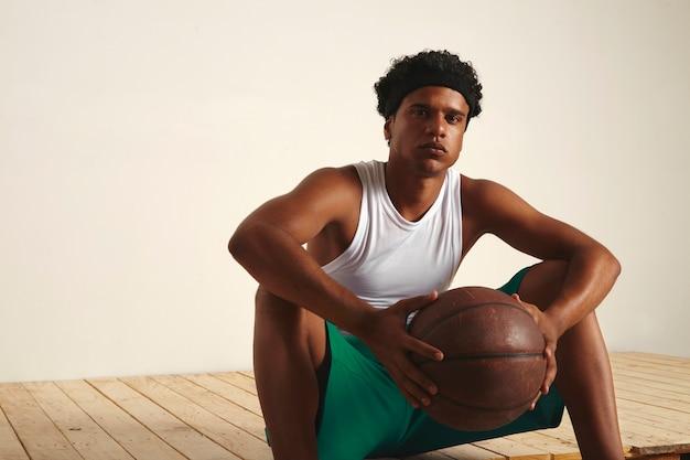 Ernsthafter müder basketballspieler, der mit einem ball in den händen auf dem boden sitzt und eine pause macht