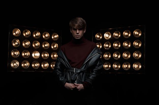 Ernsthafter mysteriöser junger mann in einer schwarzen modischen lederjacke in rotem, stilvollem golf und schwarzen jeans steht und posiert im studio in der nähe der hellen elektrischen vintage-scheinwerfer. modischer typ