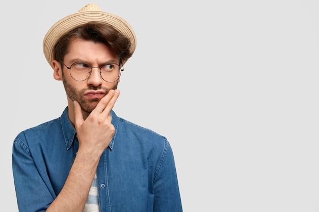 Ernsthafter nachdenklicher mann bauer hält kinn, überlegt, wie man in der landwirtschaft erfolgreich sein kann, gekleidet in stilvollen strohhut und freizeithemd
