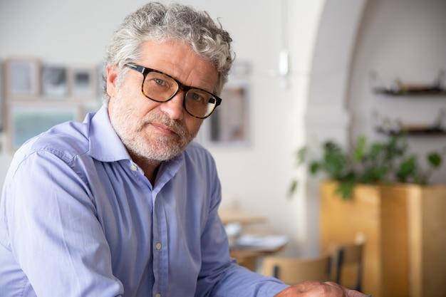 Ernsthafter nachdenklicher reifer geschäftsmann, der hemd und brille trägt und im bürocafé sitzt und kamera betrachtet