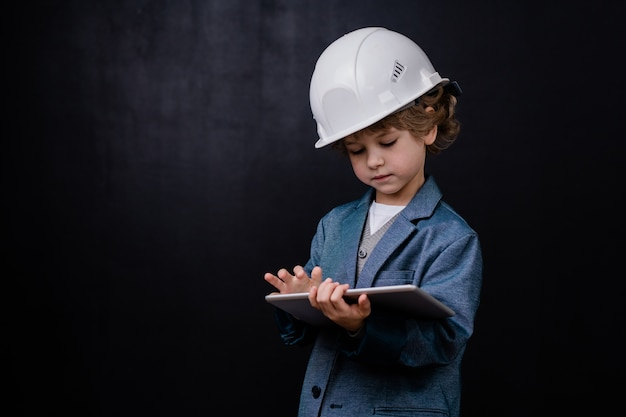 Ernsthafter niedlicher kleiner junge im helm und in der abendgarderobe unter verwendung des digitalen tablets beim surfen im netz gegen schwarzen raum
