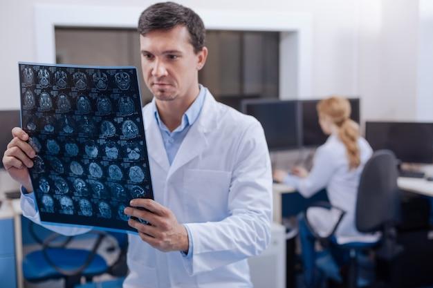 Ernsthafter professioneller männlicher arzt, der im lehrerzimmer steht und die röntgenbilder untersucht, während er in der onkologieabteilung arbeitet