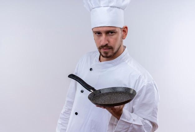 Ernsthafter professioneller männlicher koch kocht in der weißen uniform und im kochhut, der eine pfanne zeigt, die zuversichtlich steht, über weißem hintergrund zu stehen