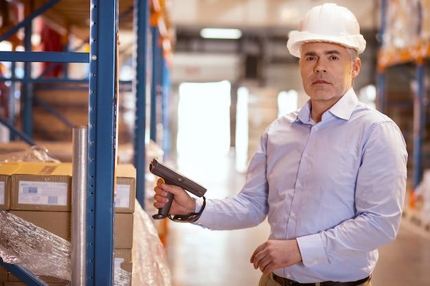 Ernsthafter professioneller mann, der sie beim halten eines scanners ansieht