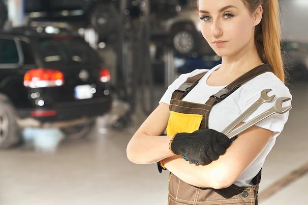 Ernsthafter professioneller mechaniker, der im autoservice aufwirft