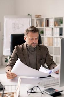 Ernsthafter reifer architekt in der abendgarderobe, der durch papiere oder blaupausen mit skizzen schaut, während er durch schreibtisch im büro sitzt
