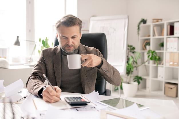 Ernsthafter reifer ingenieur oder buchhalter mit stift und tasse kaffee, die berechnungen und notizen im notizbuch im büro machen
