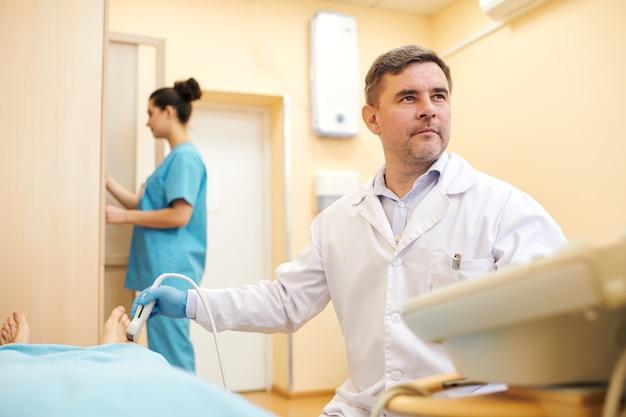 Ernsthafter reifer ultraschallspezialist in laborkittel, der die ursache von patientenschmerzen mit ultraschallgeräten in der klinik analysiert