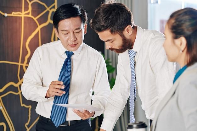 Ernsthafter reifer unternehmer, der auf finanzbericht zeigt, wenn er mit kollegen beim treffen spricht