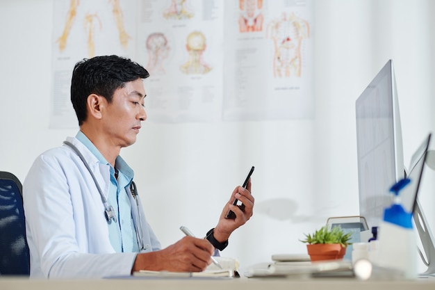 Ernsthafter reifer vietnamesischer arzt, der textnachrichten von patienten überprüft und seine beschwerden aufschreibt