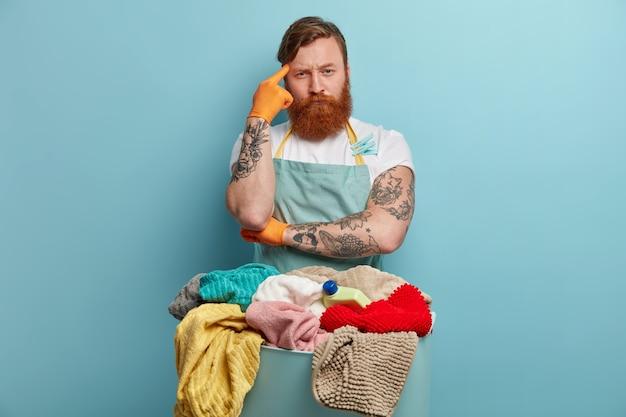 Ernsthafter rothaariger hausbesitzer denkt über etwas nach, hält den finger an der schläfe, posiert in der nähe eines beckens voller wäsche und waschmaschine, hört den waschanweisungen der frau zu und trägt eine schürze. hausarbeitskonzept