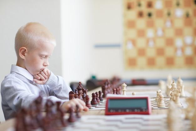 Ernsthafter schüler, der schach spielt