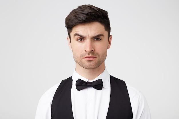 Ernsthafter selbstbewusster attraktiver mann mit kleinen stoppeln sieht selbstbewusst aus