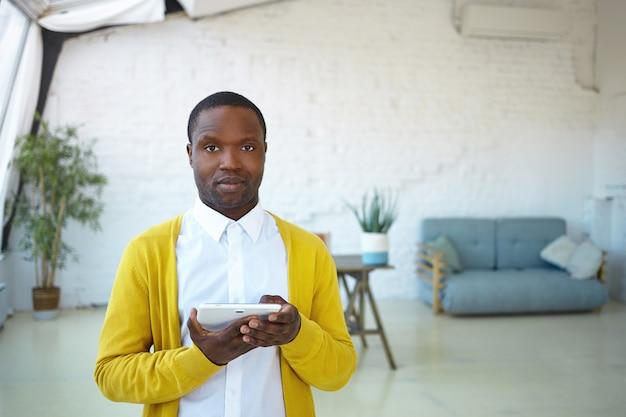 Ernsthafter, selbstbewusster junger mischlingsmann, der drinnen posiert und auf dem touchpad im internet surft. hübscher afrikanischer kerl, der wifi auf elektronischem digitalem tablett verwendet. menschen, moderner lebensstil, technologie und geräte
