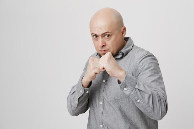 Ernsthafter selbstbewusster kahlköpfiger mann, der die fäuste ballt