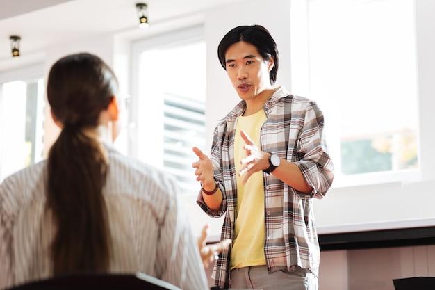 Ernsthafter sprecher. selbstbewusster junger asiatischer mann, der einen vortrag hält und selbstbewusst aussieht, während er während seiner rede gesten verwendet