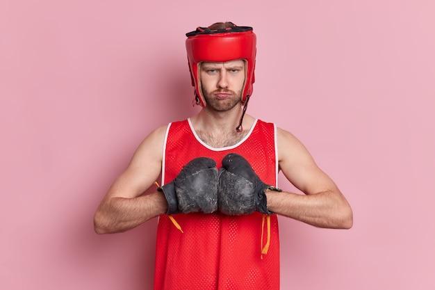 Ernsthafter starker unrasierter boxer trägt hut und boxhandschuhe hält die hände zusammen und bereitet sich auf den kampf vor.