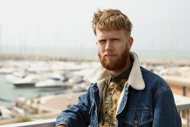 Ernsthafter stilvoller hipster-typ, der blaue jeansjacke mit zusammengekniffenen augen wegen hellem sündenlicht trägt