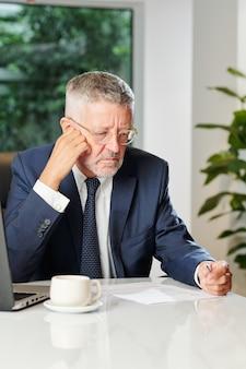 Ernsthafter stirnrunzelnder unternehmer, der morgenkaffee trinkt und geschäftsdokument liest