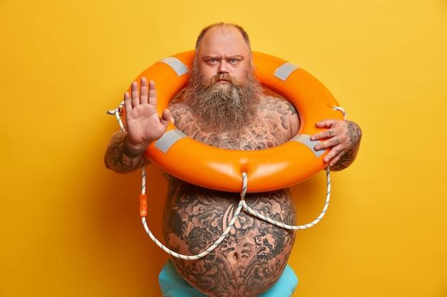 Ernsthafter strenger bärtiger mann mit nacktem fetten körper, macht ablehnung oder stoppgeste, sieht wütend aus, trägt aufgeblasenen rettungsring, verhindert unfälle auf dem wasser, posiert