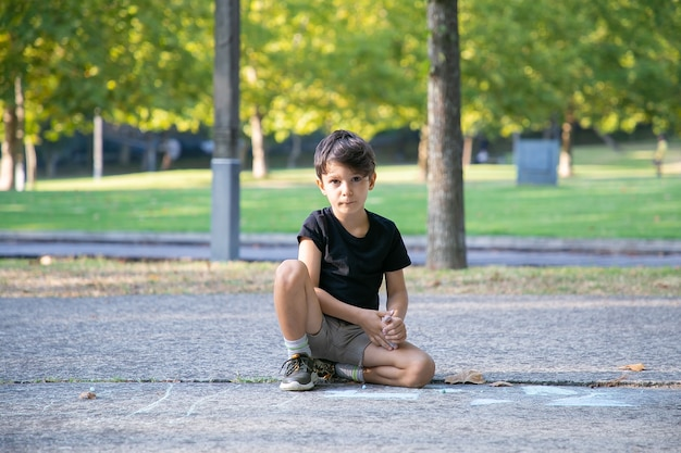 Ernsthafter süßer junge, der auf asphalt mit bunten kreidestücken sitzt und zeichnet. vorderansicht. konzept für kindheit und kreativität