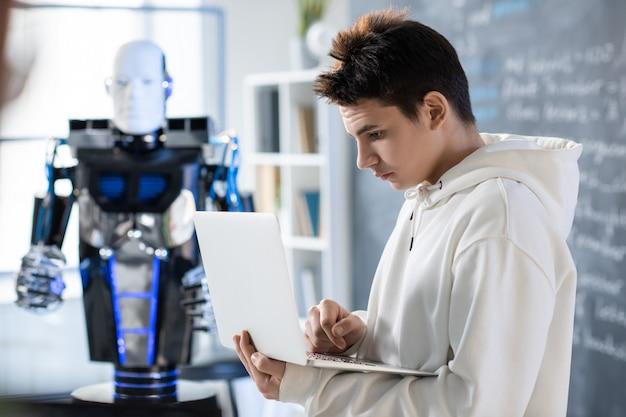 Ernsthafter teenager, der laptopanzeige beim lernen neuer software oder beim vorbereiten der präsentation auf hintergrund des roboters im klassenzimmer betrachtet