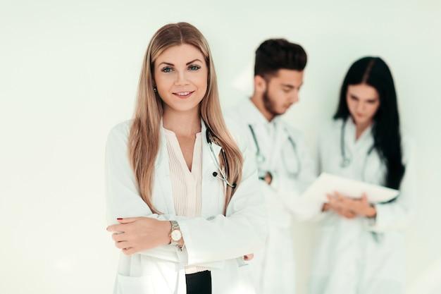 Ernsthafter therapeut mit einer zwischenablage im stehen in der klinik