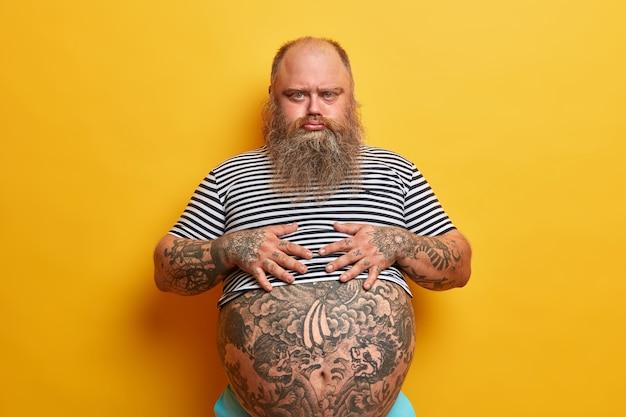 Ernsthafter, trauriger, kräftiger mann mit düsterem gesichtsausdruck, beleidigt von jemandem, besorgt über übergewicht, nicht gut für die gesundheit, hält die hände auf tätowiertem dickbauch, braucht diät-lebensstil und gewichtsverlust