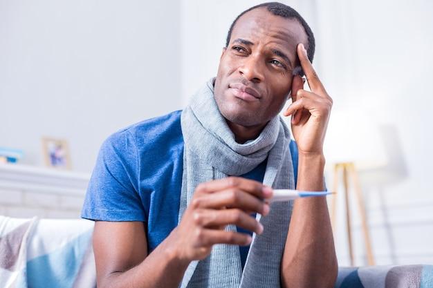 Ernsthafter trauriger nachdenklicher mann, der ein thermometer hält und seine schläfe berührt, während er kopfschmerzen fühlt