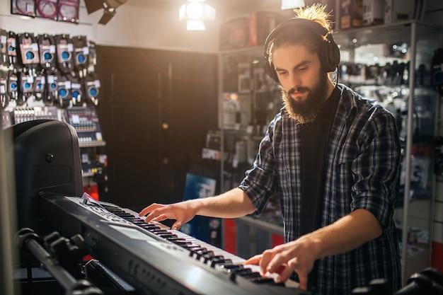 Ernsthafter und konzentrierter junger mann, der auf tastatur spielt. er hört musik über kopfhörer. innen ist es sonnig.