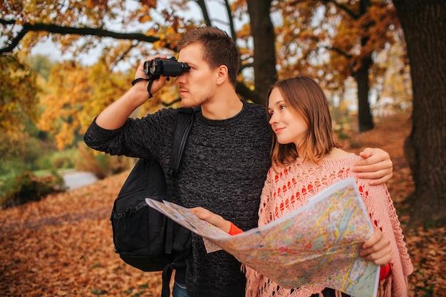 Ernsthafter und konzentrierter junger mann schaut in ein fernglas. er umarmt eine junge frau. sie hält die karte und schaut geradeaus.