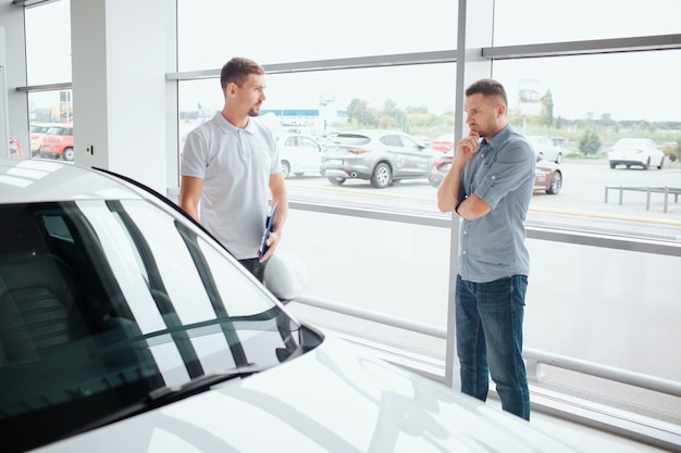 Ernsthafter und nachdenklicher junger mann stehen vor weißem auto
