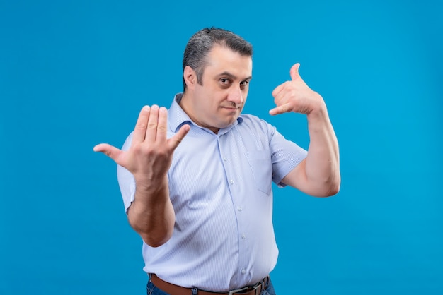 Ernsthafter und streng selbstbewusster mann mit wütendem ausdruck fordernden person treten auf einem blauen hintergrund vor