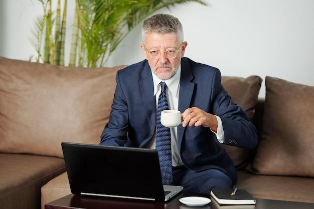 Ernsthafter unglücklicher geschäftsmann im alter, der eine tasse espesso trinkt, wenn er morgens einen videoanruf mit kollegen aus unternehmenszweigen hat
