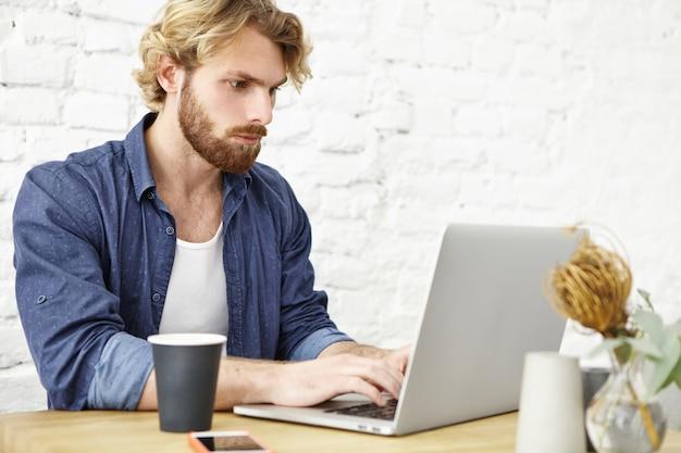 Ernsthafter unrasierter junger europäischer journalist, der am hölzernen kaffeetisch sitzt, der auf modernem laptop tastiert und wichtige informationen im internet sucht, während er an artikel für online-papier arbeitet