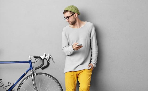 Ernsthafter unrasierter junger mann in trendiger kleidung, der an der betonwand aufwirft und sein fahrrad mit festem gang betrachtet, seine eigenschaften studiert, während anzeige über klassifizierte website veröffentlicht, zum verkauf anbietet