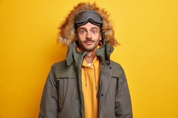 Ernsthafter unrasierter mann, der sich im winter in den bergen ausruht und gerne in warmer jacke mit pelzhaube snowboarden geht, sieht selbstbewusst aus.