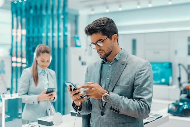 Ernsthafter unrasierter mann in abendgarderobe und mit brille, die das smartphone ausprobiert, das er kaufen möchte