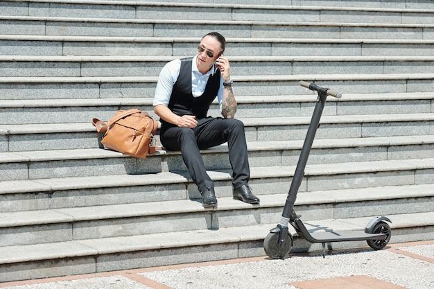 Ernsthafter unternehmer, der auf stufen sitzt, nachdem er auf roller gefahren ist und am telefon anruft