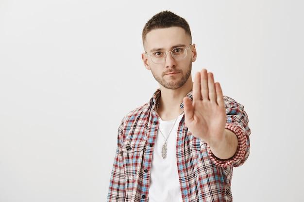 Ernsthafter unzufriedener junger mann mit brille posiert