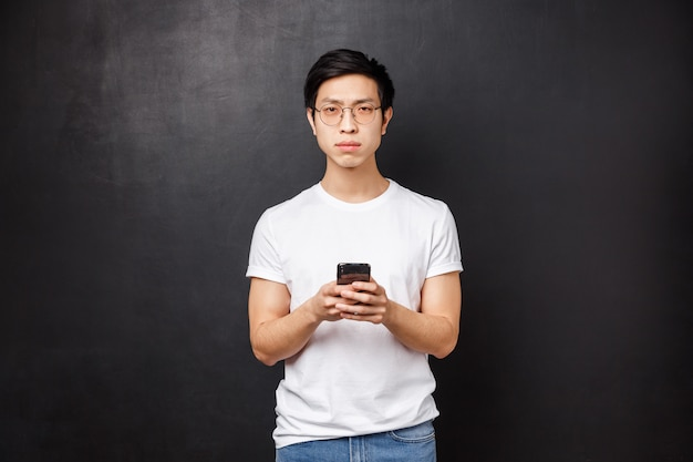 Ernsthafter verdächtiger und zweifelhafter junger asiatischer typ glaubt nicht, dass eine person online die wahrheit sagt