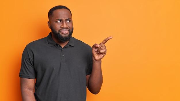 Ernsthafter verwirrter bärtiger mann zeigt weg auf leerzeichen demonstriert werbung, die in lässigen schwarzen t-shirt-posen gegen lebendige orange wand gekleidet ist