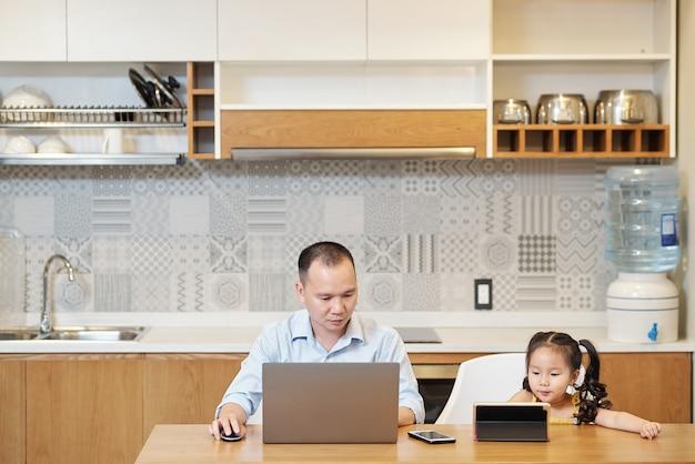 Ernsthafter vietnamesischer mann, der am laptop am küchentisch arbeitet, wenn kleine tochter cartoon auf tablet-computer neben ihm beobachtet