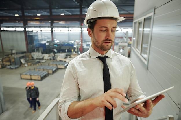 Ernsthafter vorarbeiter im helm, der ein mobiles gerät verwendet, während er in der werkstatt durch die neue technische skizze auf dem bildschirm blättert