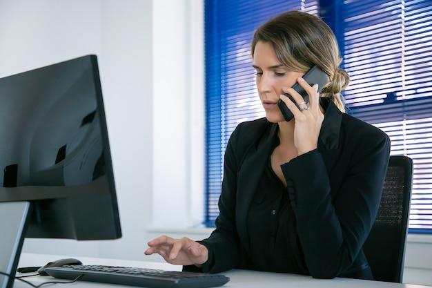 Ernsthafter weiblicher fachmann, der auf handy spricht, während er computer am arbeitsplatz im büro benutzt. mittlerer schuss. digitales kommunikations- und multitasking-konzept